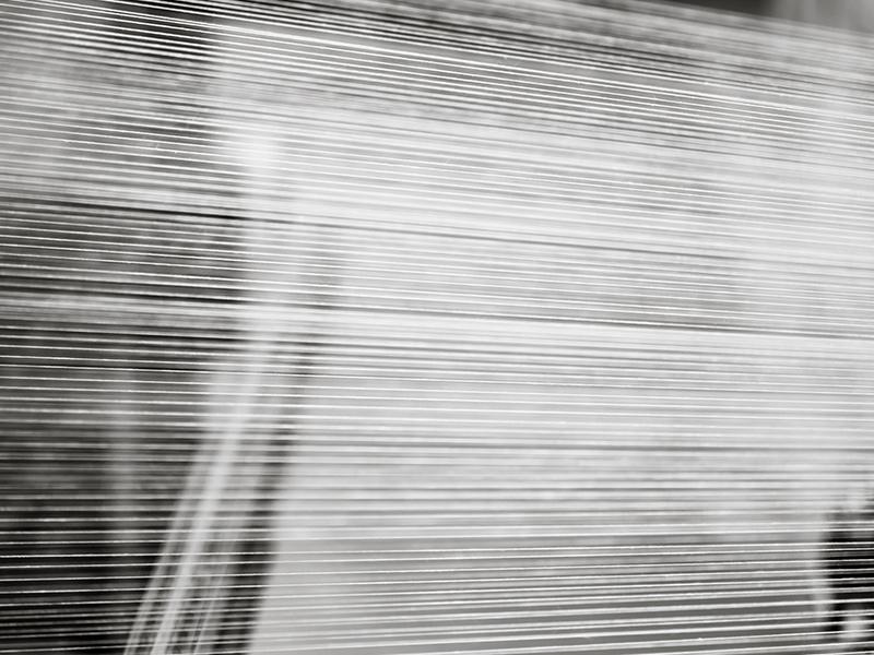 Photo de fils dans l'atelier d'un tisseur français en train de fabriquer un tissu en percale de coton